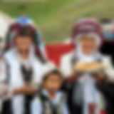 Kyrgyz_women_and_child_offering_bread_an
