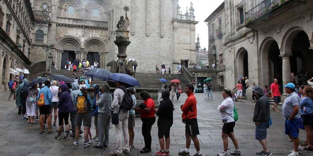 Cola de turistas esperan paraguas en mano