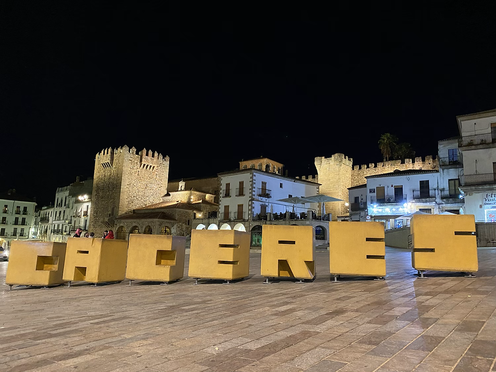 Letrero de Cáceres en la Plaza Mayor de noche