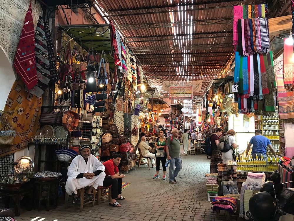 Comerciantes tratando de vender souvenirs a un grupo de turistas en el zoco de Marrakech