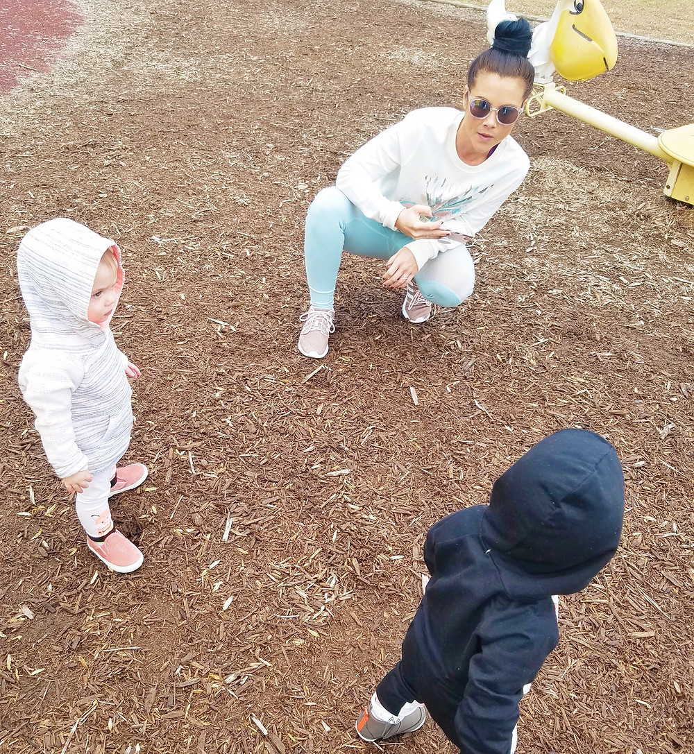 Mom in workout clothes with topknot, tending to kids at the park.