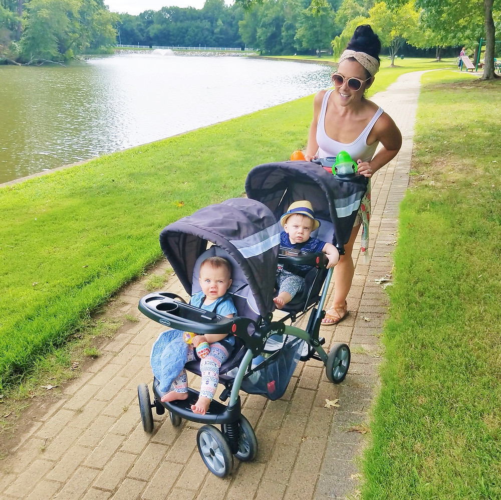 Mom with bun and headwrap pushing babies in a stroller