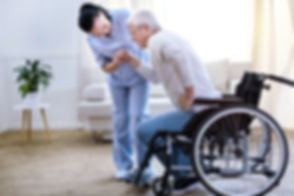 A GlobalCares home attendant helps an elderly patient sit in a wheelchair