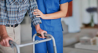 A certified nursing assistant helps an elderly man walk with a walker