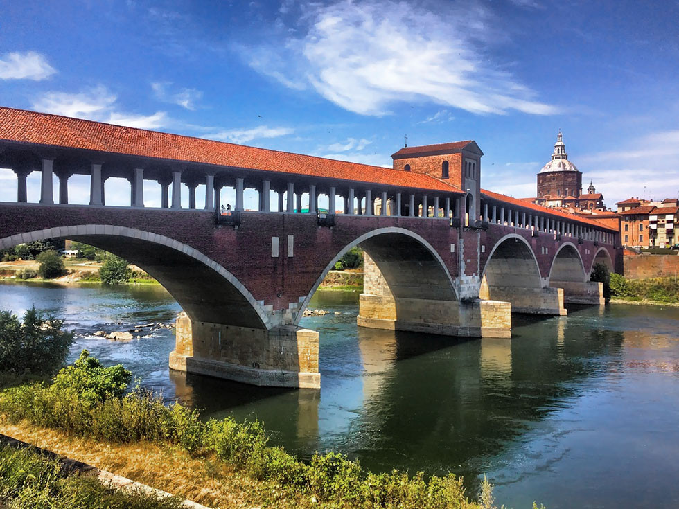 Covered bridge over the flowing waters of the Ticino River in Pavia, Italy.