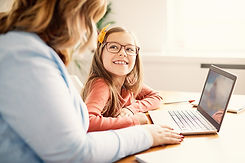 A girl and her mother watch a Simply Spanish video on their laptop