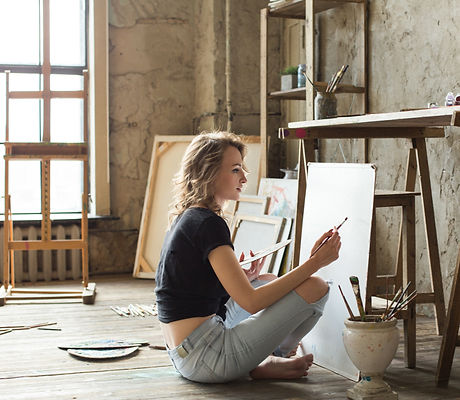Woman painter sitting on the floor in fr