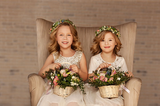 two little bridesmaid sitting in a chair
