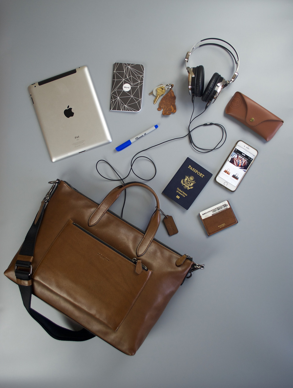 flatlay including Coach briefcase, ipad, wallet, passport, headphones, iphone, and sunglasses