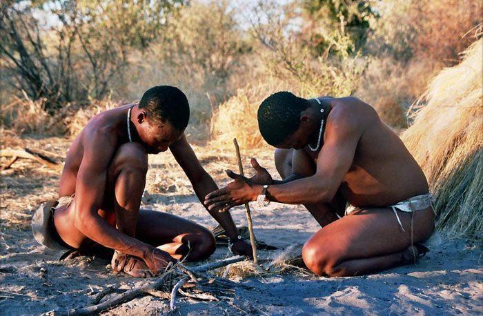 homens de uma tribo na África fazendo fogo primitivo