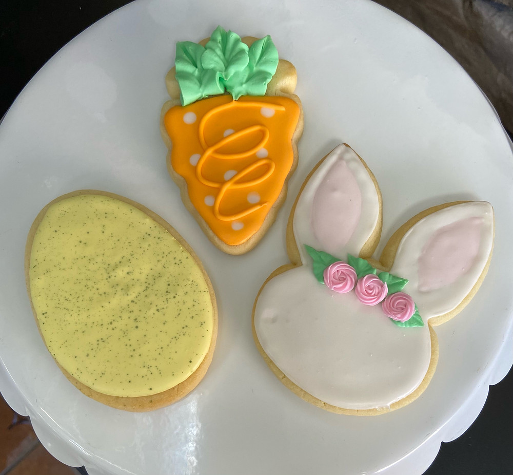 Three decorated sugar cookies; an egg with yellow frosting and sprinkles, a carrot with orange frosting, and a bunny with pink frosting.