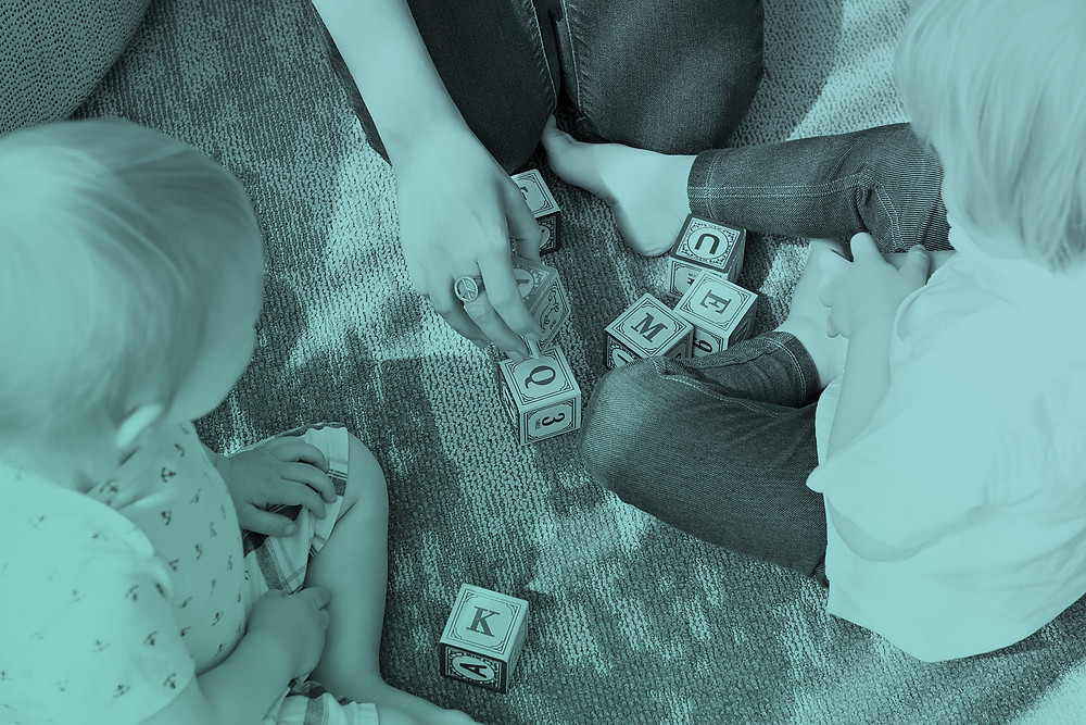 Kids and parent play with toy blocks