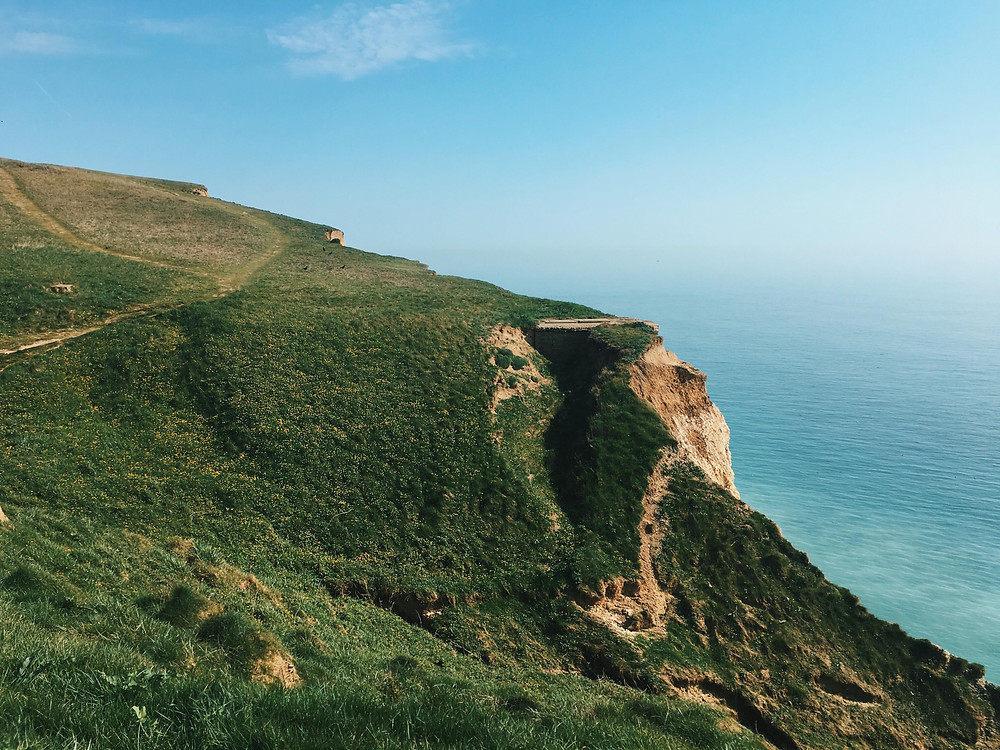 An image of a cliff path in the fore without a clear horizon in the background.