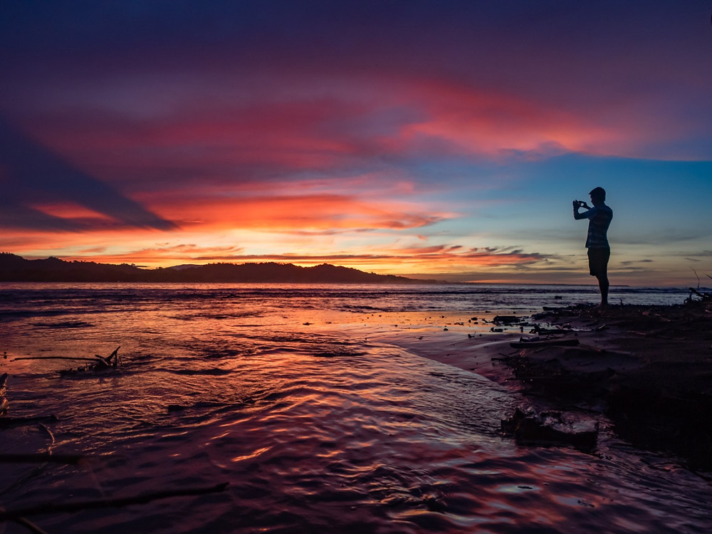 A silhouette of a person taking a picture of a spectacular sunset over Cahuita National Park in Puerto Viejo de Talamanca, Costa Rica.