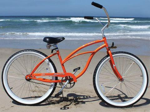 stereotypical Caribbean beach cruiser bicycle parked on the beach with the sea in the background.