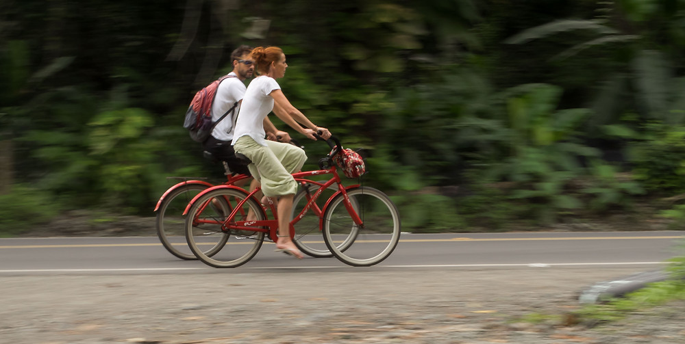 Two travelers ride matching red beach cruiser bicycles down the coastal highway in Puerto Viejo, Costa Rica