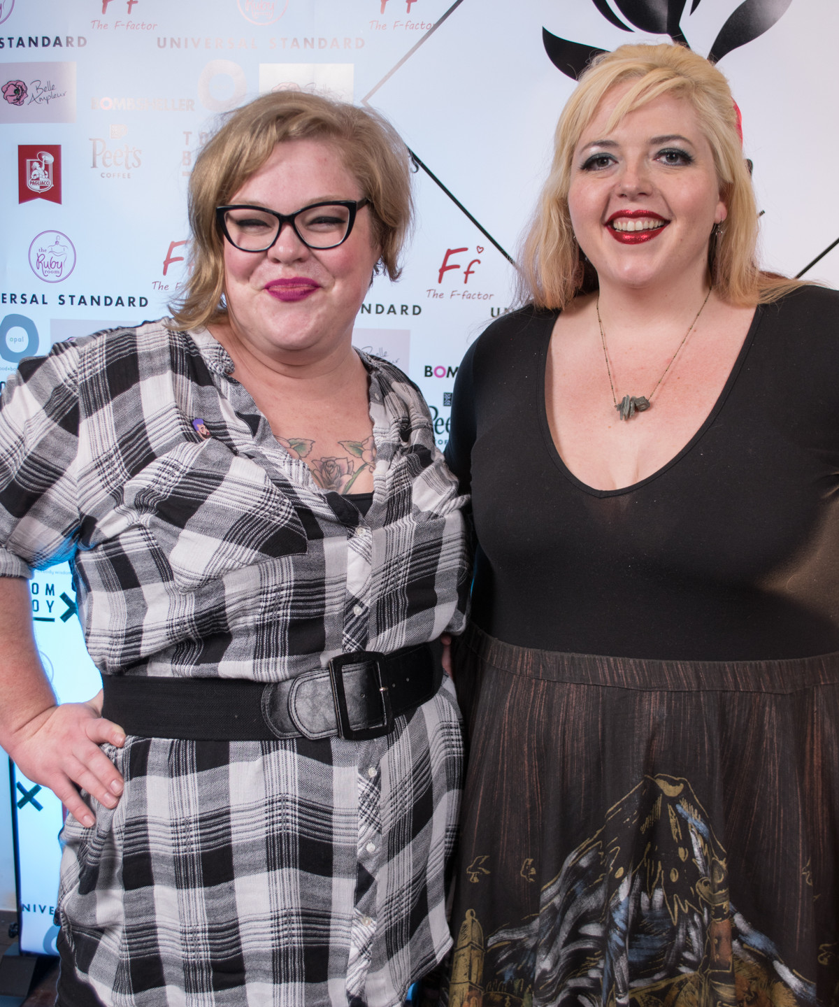 Jes of The Militant Baker and Bevin of Queer Fat Femme (and our Femmecee) pose for our step and repeat
