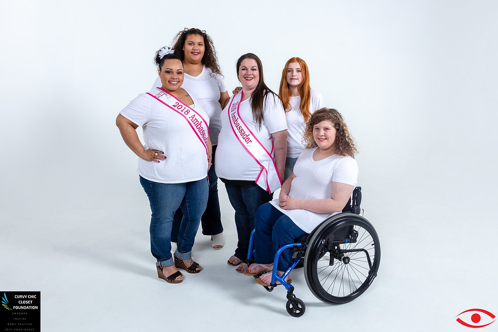 5 women in white tees and denim are pictured smiling. Two women are wearing pink and white sashes saying: 2018 Ambassador. One, on the right, is in a wheel chair