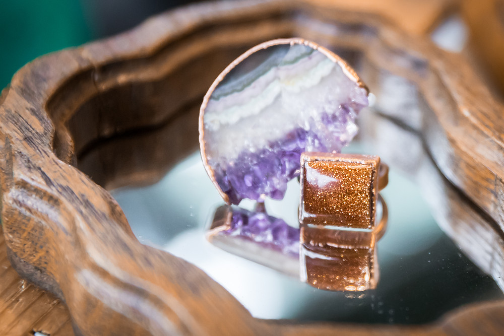 An amethyst ring and a gold stone with flecks in it rest side by side on a mirror that has a burl wood frame around it
