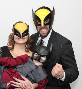 A happy family posing in custom super hero photobooth props, available with any photobooth hire package.