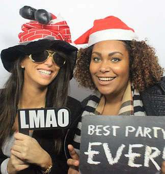 A smiling pair of ladies pose in christmas themed photo booth props; available with any photobooth hire package.