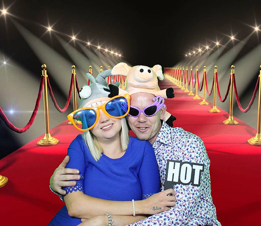 A happy couple in the greenscreen photobooth in silly costumes with a red carpet background.
