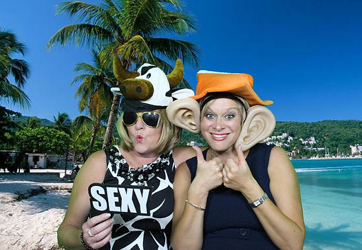 Two smiling ladies pose in the greenscreen photobooth in silly costumes with a beach scene background.