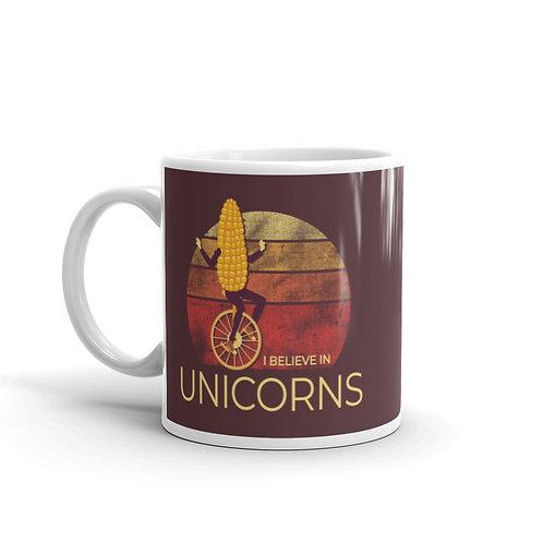 I Believe In Unicorns Funny Mug. Corn riding a unicycle.
