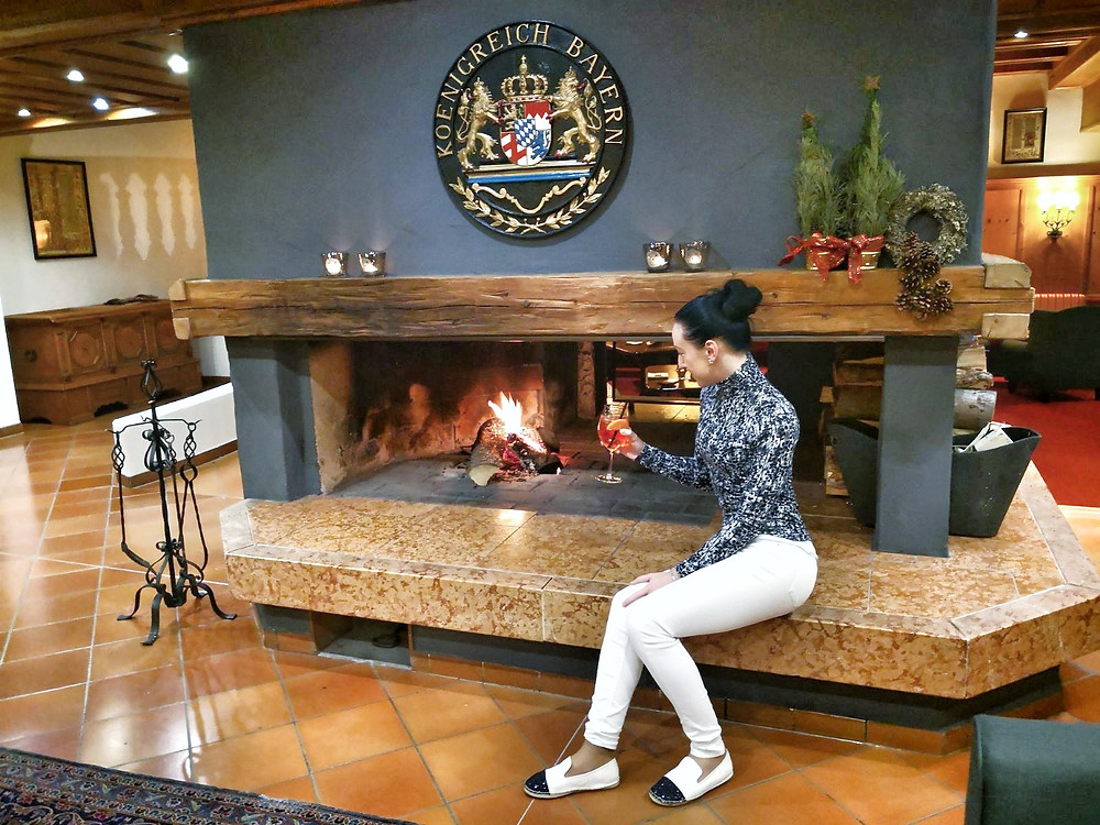 Claire by a fireplace in Riessersee hotel
