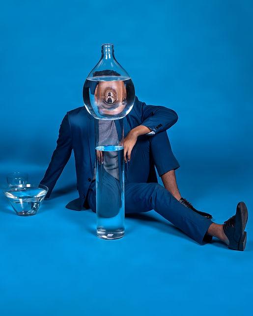 foto estudio azul ocn hombre vestido de azul, vasos lo deforman