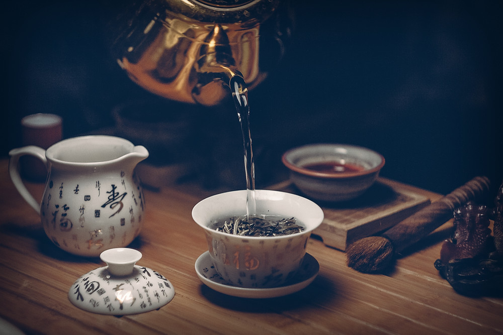 An image of a scene with a tea set, on top of a wooden table, with a silver pot appearing to pour hot water into a tea cup filled with dried tea.