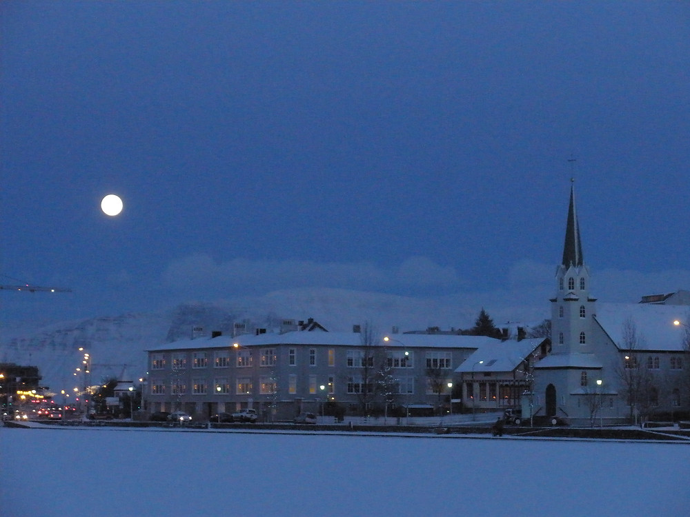 A large full moon hangs over Reykjavík, Iceland at dusk.  There are snow covered buildings and a church with a tall steeple along the snow-covered frozen pond in the center of town. The sky is a medium blue and mountains are visible in the background.