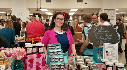 A smiling woman with dark hair and glasses is wearing a teal dress and pink sweater while she stands behind a table with a display of jam jars and gift packs
