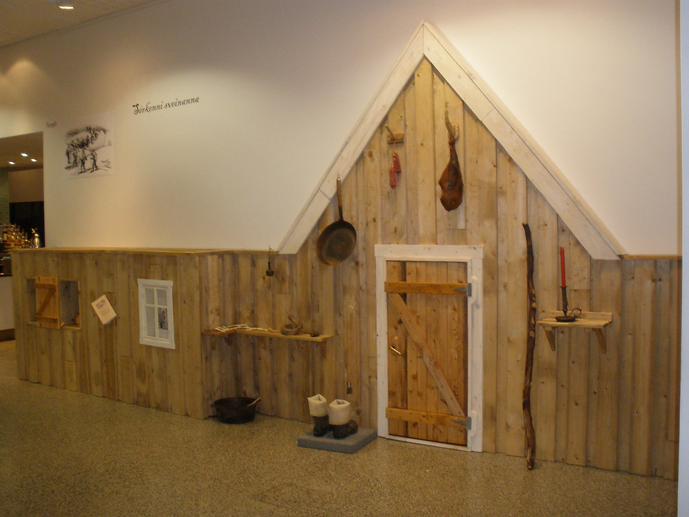 Replica of a traditional Icelandic home inside of a museum. There is a wood door, candle, and pots, pans, and smoked meat hanging on the wood paneled walls.