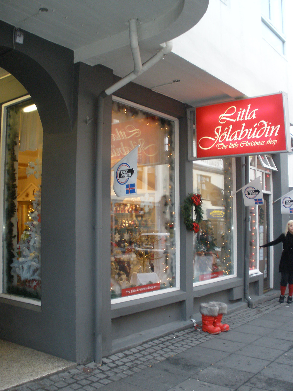 "A grey storefront in Reykjavík, Iceland, with a red sign and white lettering, and a stone sidewalk. The store name translates to ""Little Christmas Shop"". You can see a variety of ornaments and decorations behind the large glass windows."