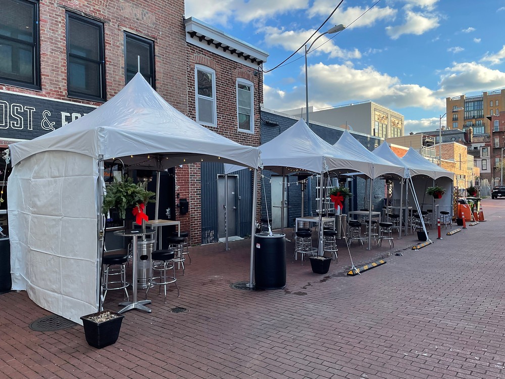 A row of open-sided large white tents lines a wide brick alley outside a row of brick storefronts. Each tent has strands of large outdoor lights and silver high-top tables with black bar stools under them. There are also pine holiday wreaths with bright red bows on each tent. There are small white clouds dotting a blue sky.