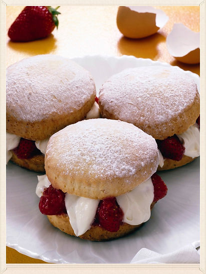 Three mini strawberry shortcakes are on a white plate with a strawberry and eggshell in the background