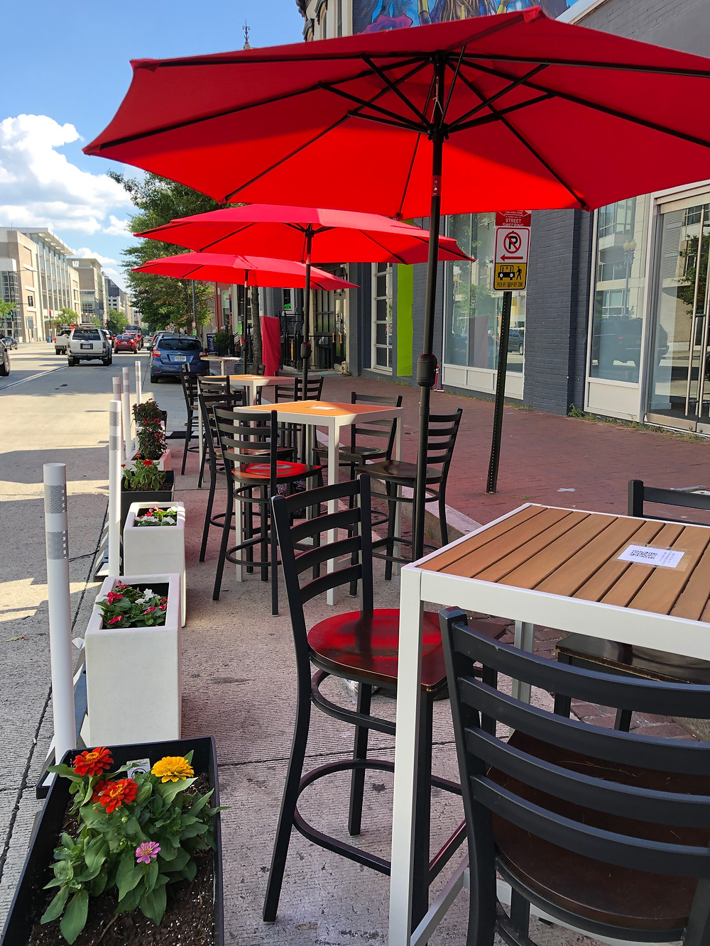 A row of patio dining high-top tables with black bar chairs line the street outside of a bar on a bright sunny day. Each table has a large bright red umbrella. White planter boxes with bright flowers create a border between the seating area and traffic.