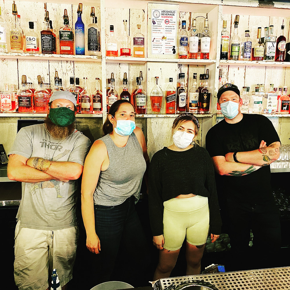 Four people wearing surgical face masks are standing behind a bar. There are two women in the center, and men on both ends. They are all dressed casually in t-shirts, tank tops, and jeans. Behind them are white distressed wood bar shelves filled with bottles.