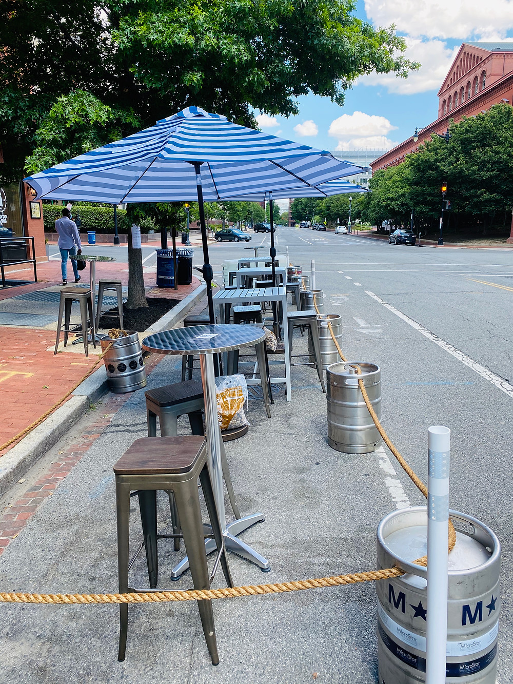 Several silver high-top tables with stools are set up in a roped off area of the street next to a brick sidewalk. There are large blue and white striped umbrellas between each table. A thick brown nautical rope is strung through large silver keg handles to section off the seating area from traffic. There are green trees along the next block in the distance.