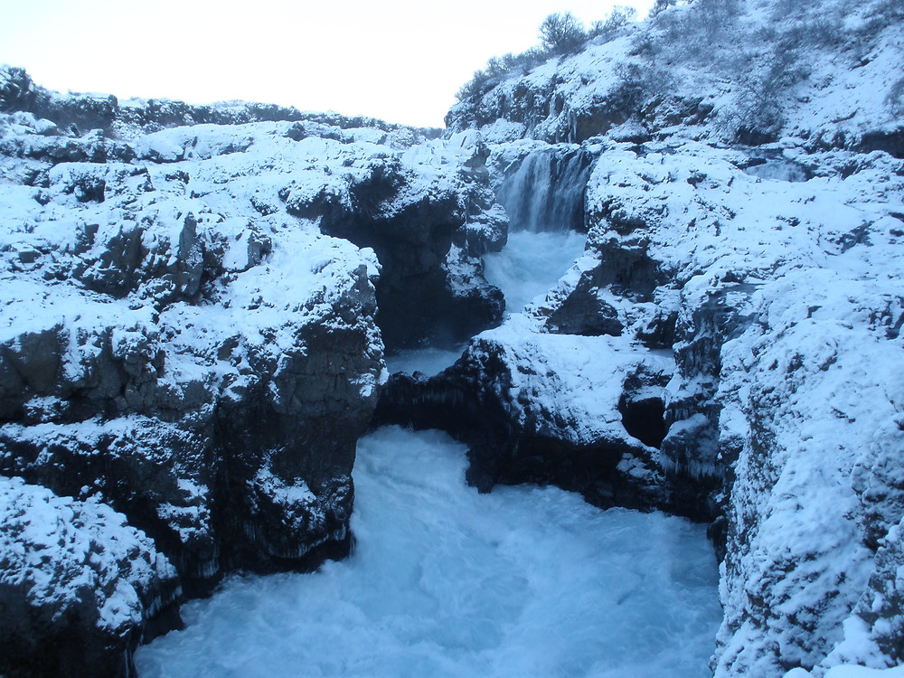 A waterfall and rushing waters cut through snow-covered rocks. The sun was setting, giving the snow and sky a bluish tint.