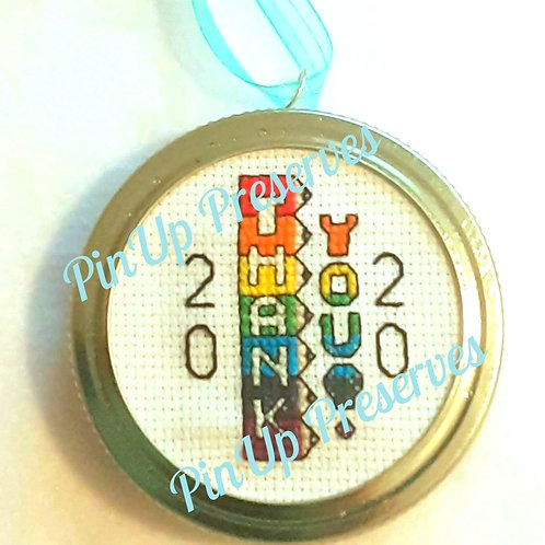 "Cross-stitch school theme ornament of stacked sharpened rainbow pencils spells ""Thank you!""; black line ""20"" on both sides."
