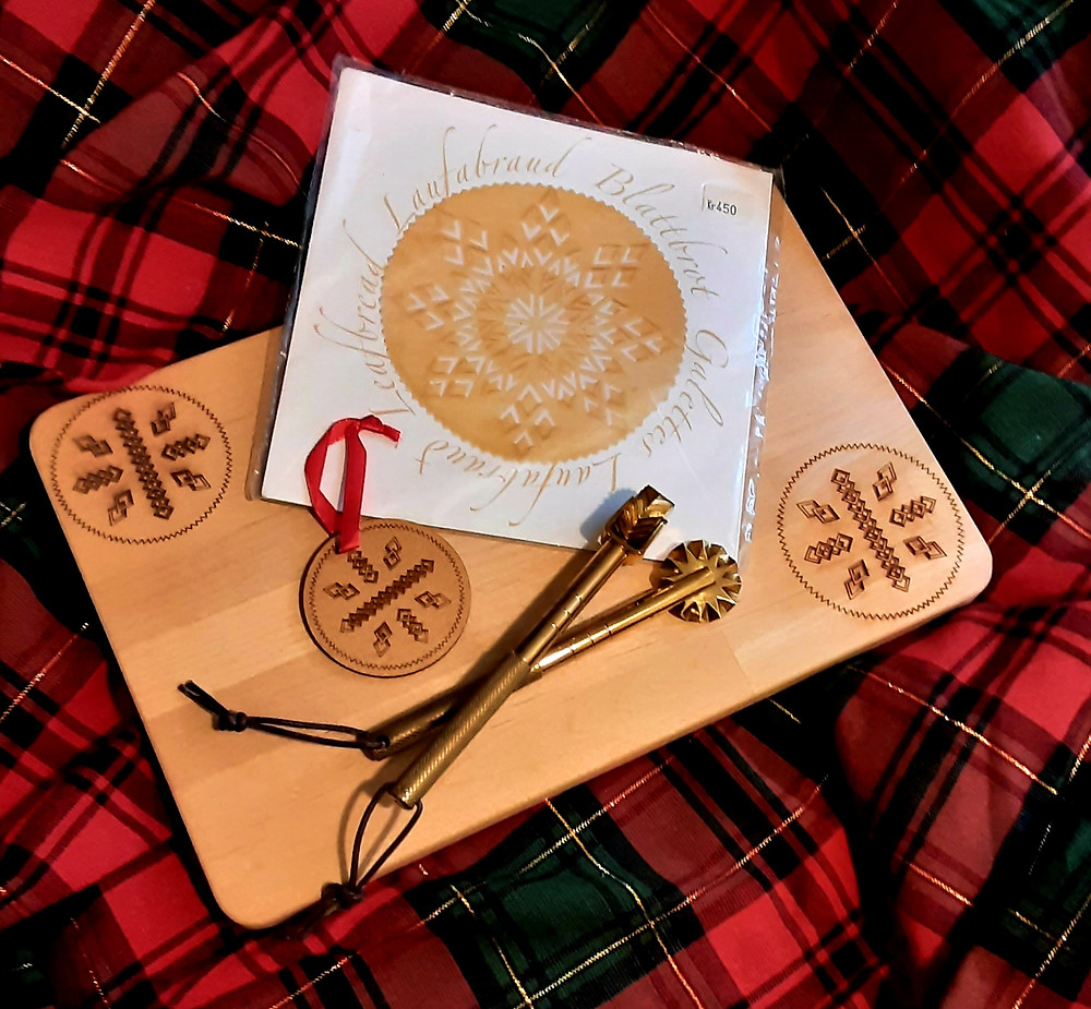 Wooden cutting board and ornament with laufabrauð design and two laufabrauðsjárn on a red and green plaid cloth background.