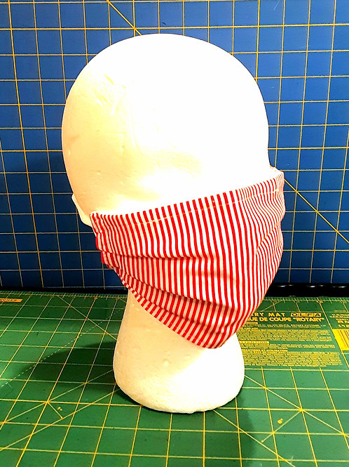 Red and white candy stripe face mask pinned to styrofoam display head with blue cutting mat background