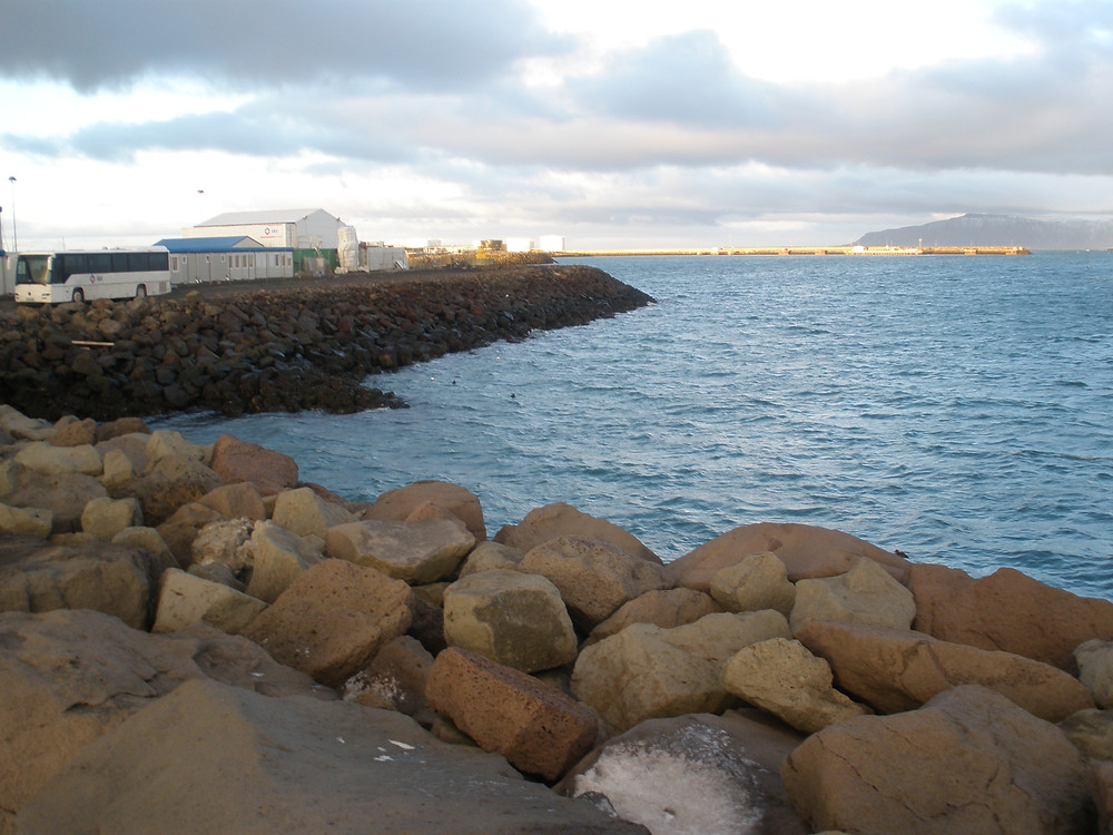 Rocky coast of the harbor in Reykjavík, Iceland, meeting dark blue waters. The shoreline curves to the side, then to the center, forming a point. Large grey clouds and snow covered mountains are in the distance.