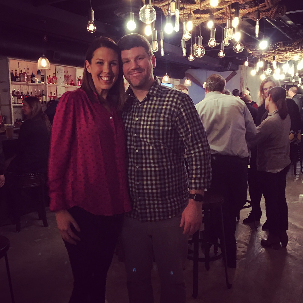 A smiling man and woman stand together with their arms around one another and facing the camera. She is wearing a red blouse and black pants. He has on a blue checked button down shirt and khakis. The room behind them is filled with happy people and elaborate lights hang from upcycled shipping nets along the ceiling. There are fully stocked bar shelves behind them to the left.
