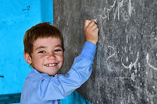 UNI303882 - boy smiling and writing on b