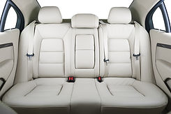 Back passenger seats in modern luxury car, frontal view, white leather.jpg