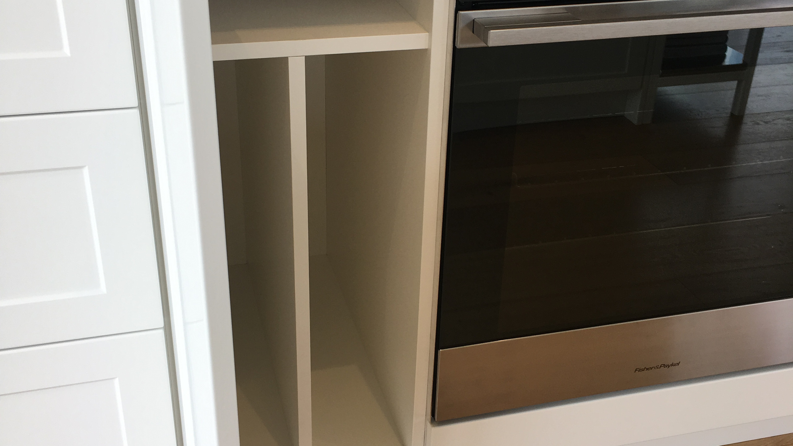 Located just next the oven to store those additional oven trays