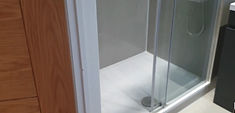 A bnew shower cubical with grey surround and a whire shower base, located in London